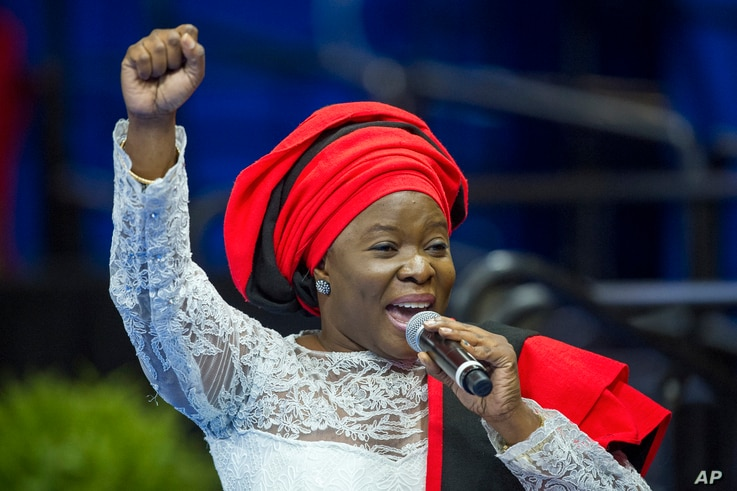 African singer Grace Alache Jerry raises her fist as she introdices President Barack Obama to speak at the Young African Leaders Initiative presidential summit in Washington, Aug. 3, 2015.