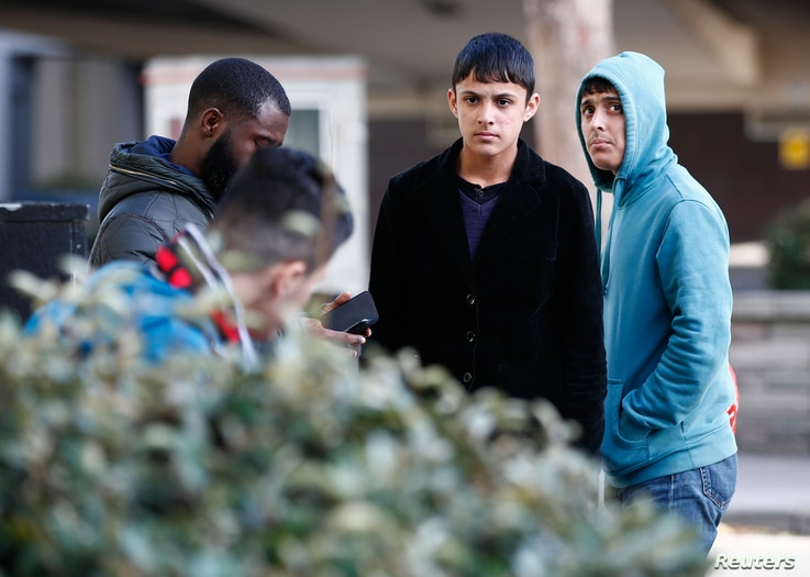 Two members a group of unaccompanied minors (R and 2nd R) from the Jungle migrant camp in Calais stand outside an immigration centre after being processed after their arrival in Britain, in Croydon, south London, Oct. 18, 2016.