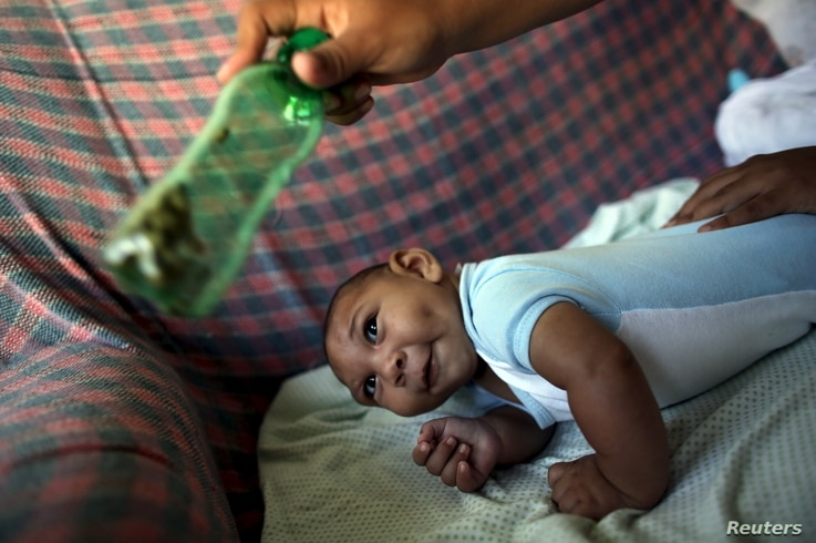 Jackeline, 26, uses a green bottle to stimulate to her son Daniel who is 4-months old and born with microcephaly, inside of their house in Olinda, near Recife, Brazil, Feb. 11, 2016.
