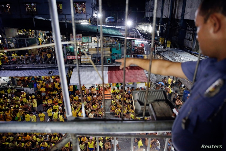 FILE - A guard points at inmates gathered at the basketball court for a head count before going to sleep at Quezon City Jail in Manila, Philippines, Oct. 18, 2016.