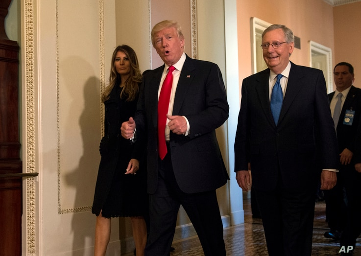 FILE - President-elect Donald Trump, accompanied by his wife Melania, and Senate Majority Leader Mitch McConnell of Ky., gestures while walking on Capitol Hill in Washington, November. 10, 2016. Washington's new power trio consists of a bombastic b...