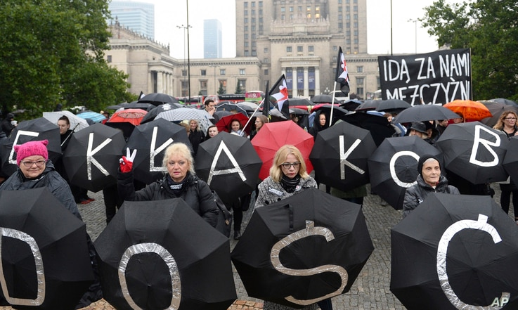 Women holding umbrellas march through downtown Warsaw to protest efforts by the nation's conservative leaders to tighten Poland's already restrictive abortion law, Oct. 3, 2017.