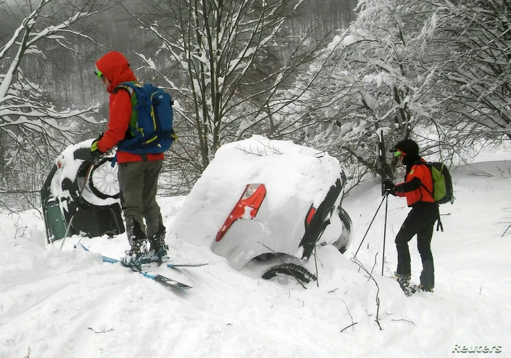 Members of Lazio's Alpine and Speleological Rescue Team are seen next to cars covered in snow in front of the Hotel Rigopiano in Farindola, Italy, that was hit by an avalanche, Jan. 19, 2017.