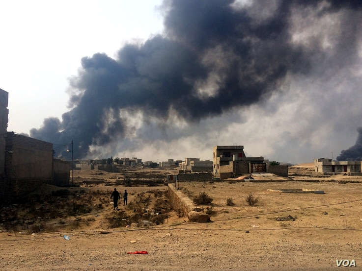 In Qayyarah, Iraq, smoke from burning oil wells burns over the city after being set on fire again by Islamic State militants. October 24, 2016. (H.Murdock/VOA)