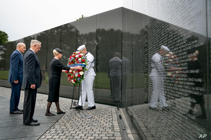 Cindy McCain, wife of Sen. John McCain, accompanied by President Donald Trump's Chief of Staff John Kelly (L) and Defense Secretary Jim Mattis (2-L) lays a wreath at the Vietnam Veterans Memorial in Washington, Sept. 1, 2018.