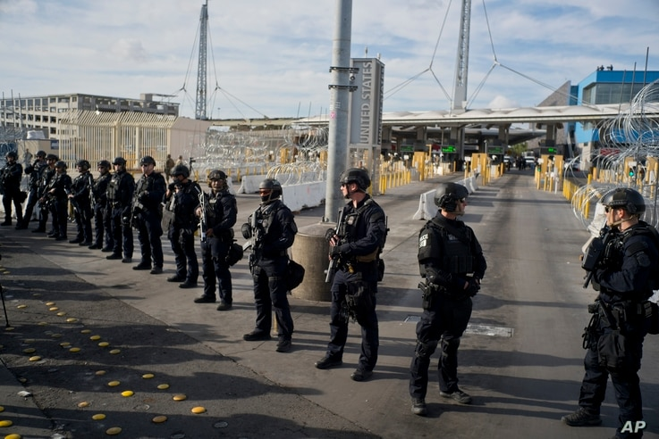 U.S. Customs and Border Protection agents stand guard at the San Ysidro port of entry on the U.S.-Mexico border, seen from Tijuana, Mexico, Nov. 22, 2018.