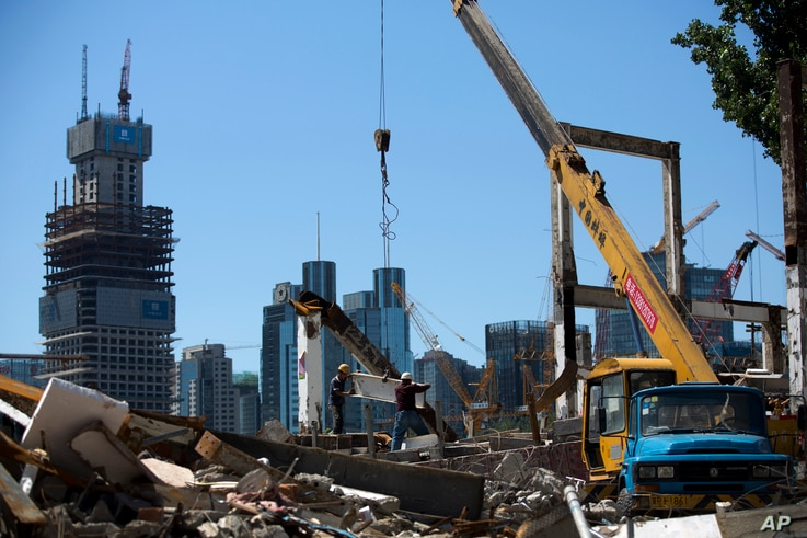 FILE- Workers move a steel frame on a demolished site for a new development project at the central business district of Beijing, China, June 30, 2015. The U.N. is concerned that human rights safeguards will not be a priority on China-backed developme...