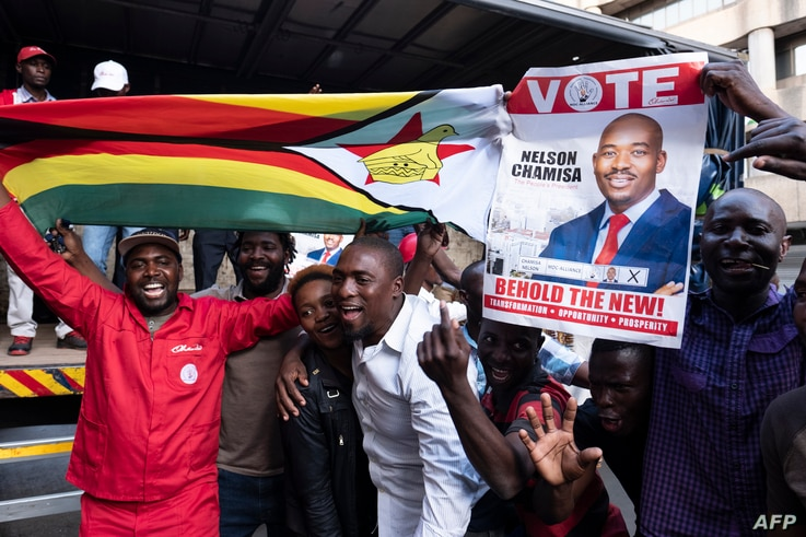 Supporters of MDC (Movement for Democratic Change Alliance) leader and opposition presidential candidate cheer outside the MDC headquarters in Harare, on July 31, 2018.
