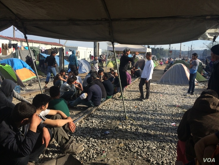 Protesters sit on the train tracks, keeping the trains from going from Greece to Macedonia in Idomeni, Greece, March 30, 2016.  (Photo - H. Murdock/VOA)