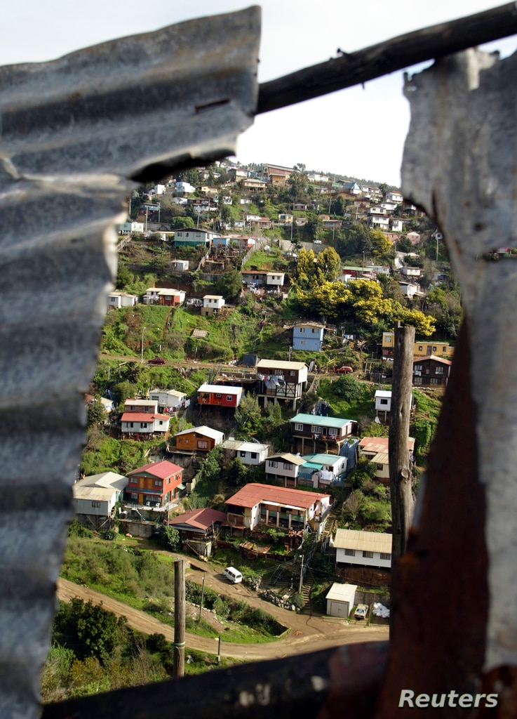 A low-income neighborhood is seen through the roof of a shanty on a hillside in the Chilean coastal city of Valparaiso on June 29, 2005.