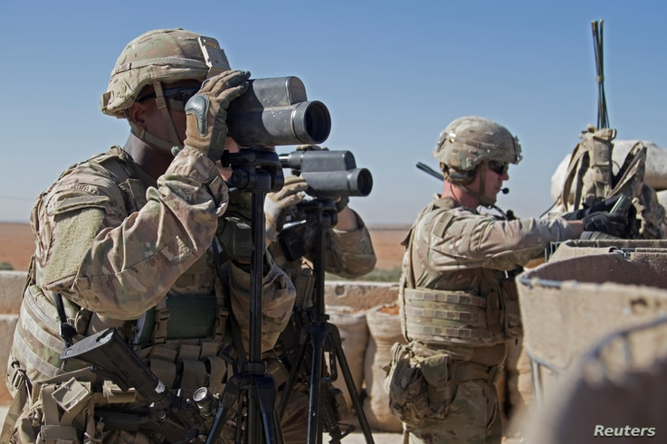 FILE - U.S. Soldiers scan the area during a combined joint patrol in Manbij, Syria, Nov. 1, 2018.