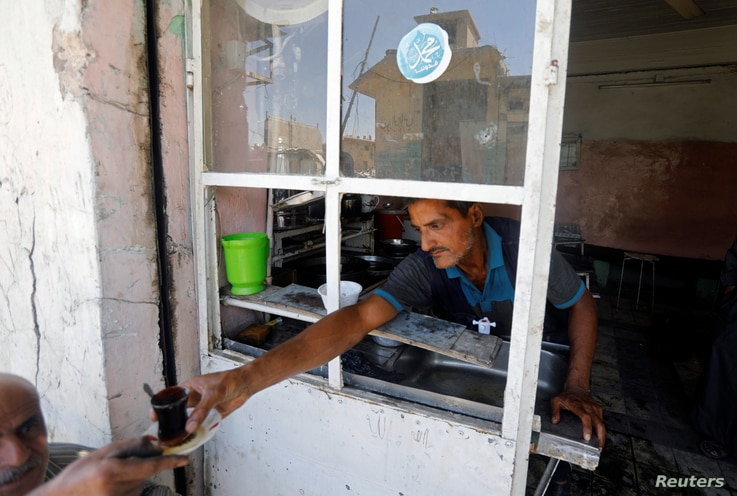 An Iraqi man distributes tea for people at a cafe in the destroyed Old City of Mosul, Iraq, Aug. 7, 2017.