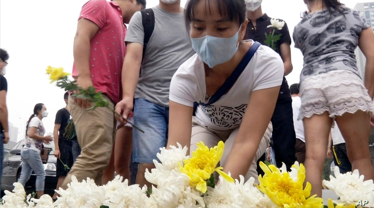 Residents of the Harbour City apartment complex place flowers at a memorial near their building for victims of the Tianjin blasts in northeastern China's Tianjin municipality, Aug. 18, 2015.