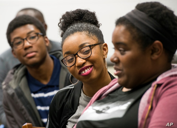 FILE - Google software engineer and Google In Residence Sabrina Williams, right, talks with freshman Alanna Walton during a class at Howard University in Washington. Acheivement gaps that begin at lower levels of schooling can continue into college.