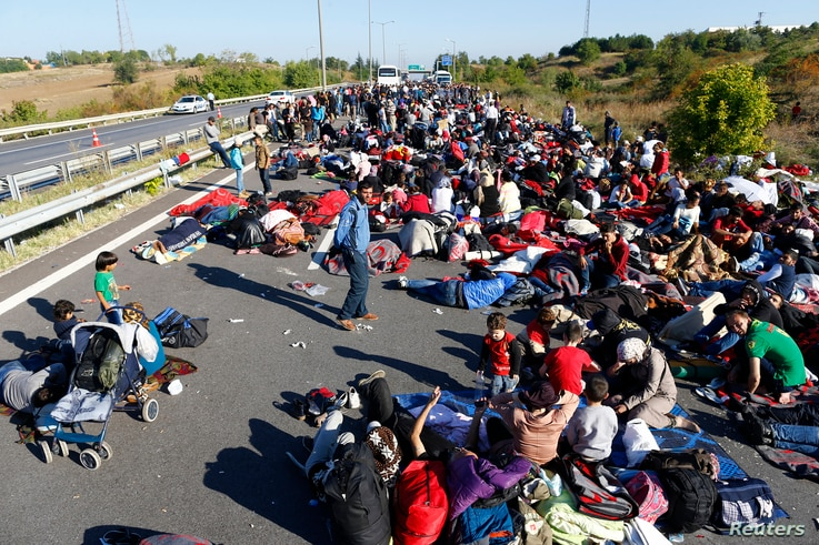 FILE - Men, women and children gather on a highway which is blocked by Turkish police and gendarmes near Edirne, Turkey, Sept. 19, 2015.