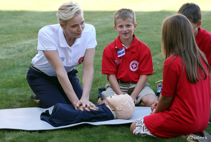 Monaco's Princess Charlene, goodwill ambassador for the International Federation of Red Crosses and Red Crescents Societies (IFRC) for first aid, demonstrates on a dummy how to practice first aid to chidren during the launch of World First Aid Day 20...