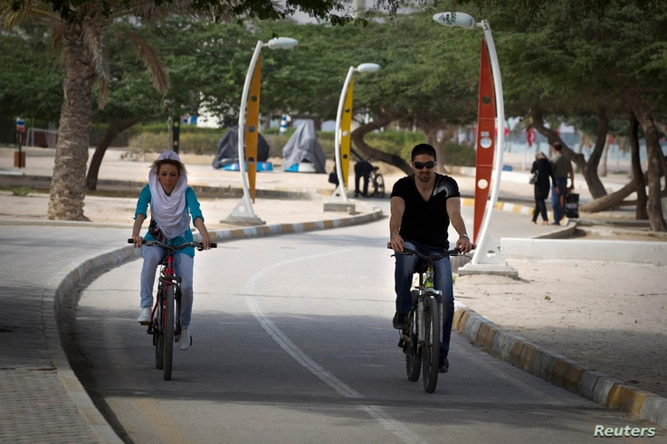 FILE - A couple rides bicycles on a bike path in Kish Island, approximately 1,250 kilometers (777 miles) south of Tehran, April 26, 2011.
