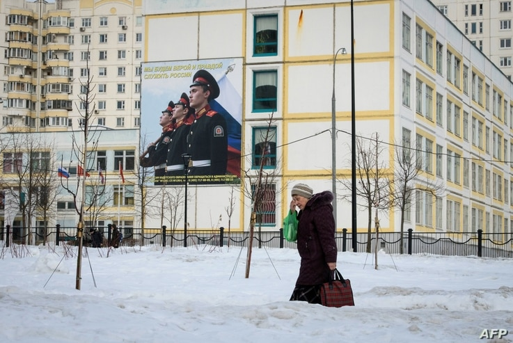 FILE - A woman carrying bags of groceries walks past a school building with a military-themed poster in front of it, on the outskirts of Moscow, Russia, Feb. 27, 2019.