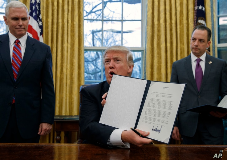 FILE - In this Jan. 23, 2017, photo, Vice President Mike Pence, left, and White House Chief of Staff Reince Priebus, right, watch as President Donald Trump shows off an executive order to withdraw the U.S. from the 12-nation Trans-Pacific Partnership...