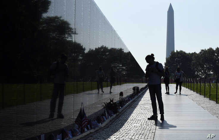 With the Washington Monument in the background, people visit the Vietnam Memorial in Washington on May 27, 2016, on the start of the Memorial Day weekend.