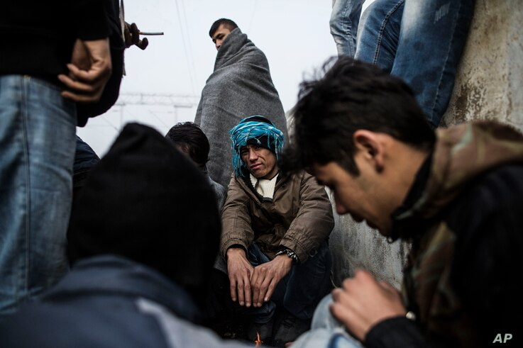 A group of Afghan refugees warm themselves near a fire at at the railway station of Sid, Serbia, where Serbian authorities send them to Croatia, Nov. 6, 2015.