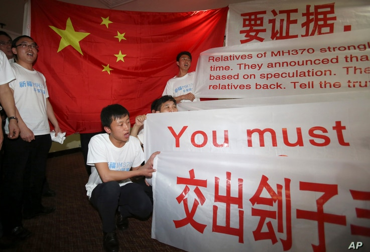 Newly arrived Chinese relatives of passengers on board the missing Malaysia Airlines flight MH370 shouts slogans as they speak to reporters at a hotel in Subang Jaya, Malaysia, Sunday March 30, 2014.