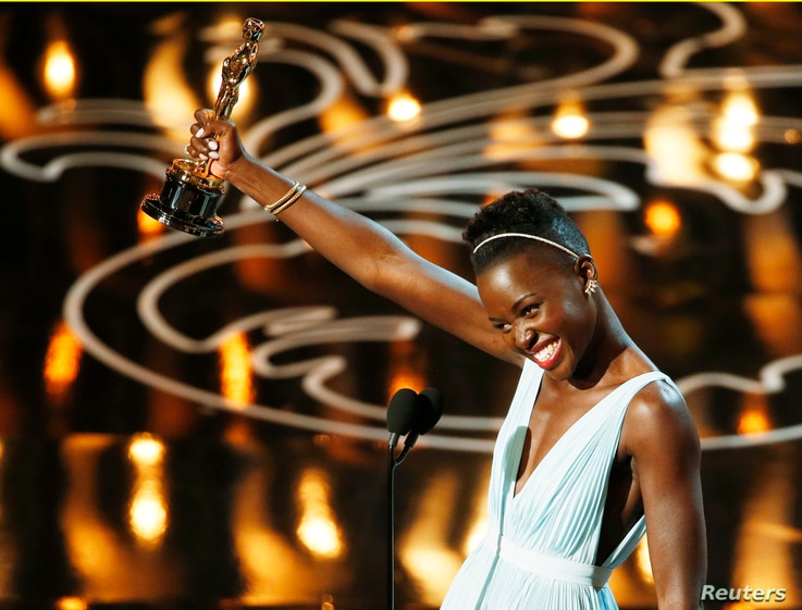 """Lupita Nyong'o, best supporting actress winner for her role in """"12 Years a Slave"""", speaks on stage at the 86th Academy Awards in Hollywood, CA. March 2, 2014."""