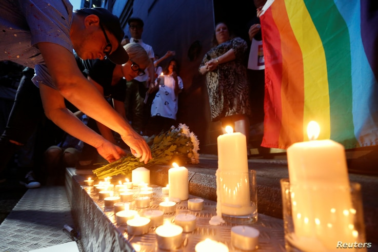Singers Anthony Wong, left, and Denise Ho, who have announced their homosexual status, lay flowers during a candlelight vigil to mourn victims of the Pulse Orlando shooting, Hong Kong, China, June 13, 2016.