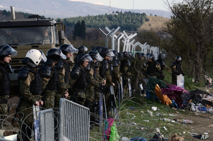 Macedonian policemen guard the borders of their country as an army truck arrives to build a border fence to prevent illegal crossings by migrants, in the Greek-Macedonian border near the Greek village of Idomeni, Nov. 28, 2015.