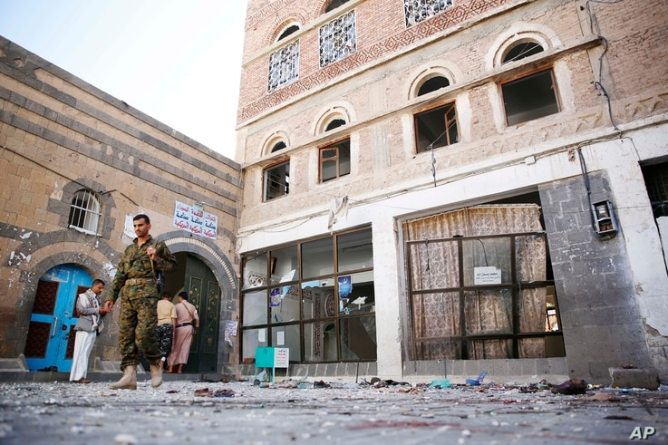 Shiite fighters, known as Houthis, inspect the the scene at the al-Balili mosque after two suicide bombings at the mosque during Eid al-Adha prayers in Sanaa, Yemen, Thursday, Sept. 24, 2015.