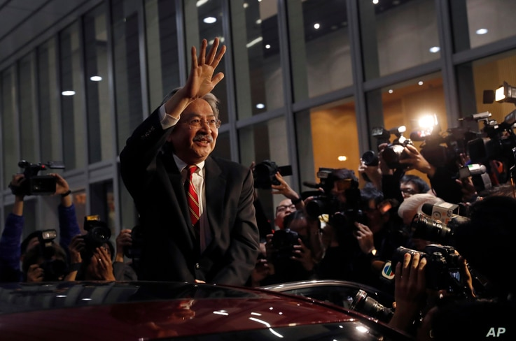Hong Kong's Financial Secretary John Tsang waves to reporters as he leaves his office in Hong Kong, Dec.12, 2016.
