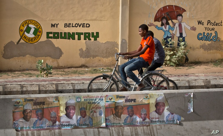 Two youths ride bicycles past a mural on a school wall and election posters supporting President Goodluck Jonathan, on a street in Kano, Nigeria Sunday, March 29, 2015.