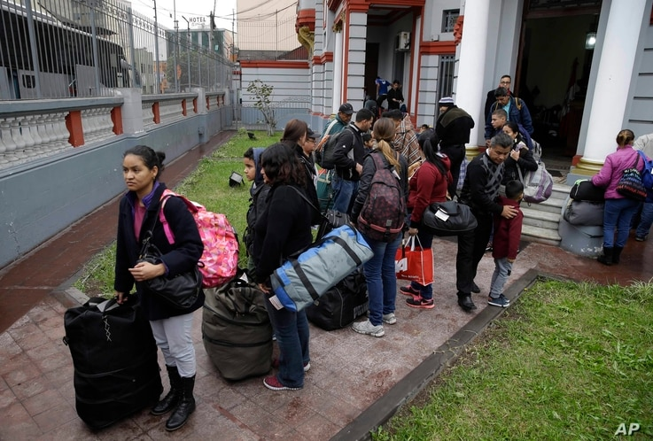 Venezuelan migrants wait outside their country's embassy for a bus that will transport them to the airport, in Lima, Peru, Aug. 27, 2018.