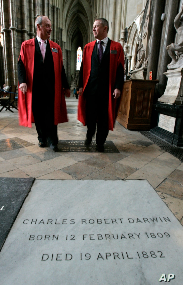 FILE - Two cathedral guides walk toward the grave of Charles Darwin at Westminster Abbey, in London, Feb. 4, 2009.