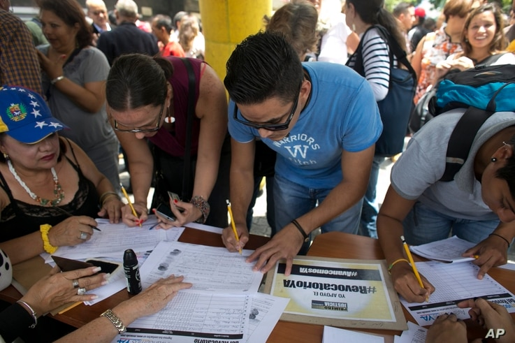 FILE -People sign a petition, organized by the opposition, to initiate a recall referendum against Venezuela's President Nicolas Maduro in Caracas, Venezuela, April 27, 2017.