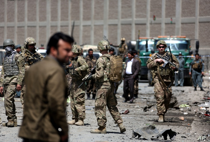 FILE - US forces and Afghan security inspect the site after a suicide bombing attack near Kabul's international airport in Kabul, Afghanistan, May 17, 2015.