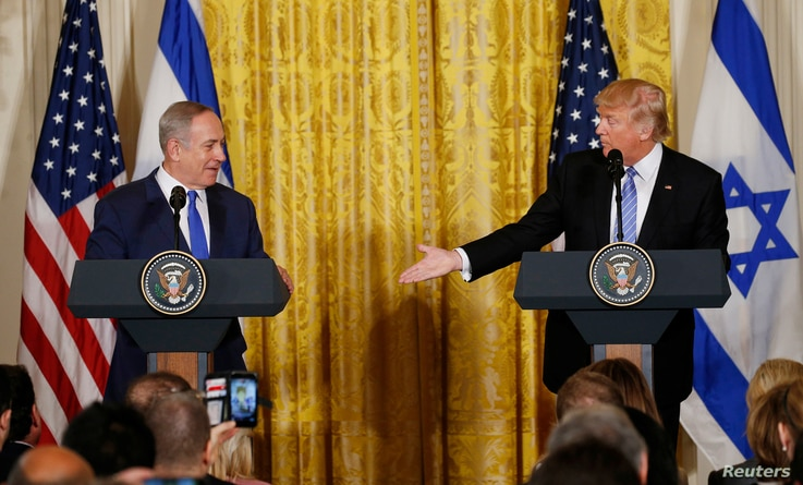 U.S. President Donald Trump, right, reaches out to Israeli Prime Minister Benjamin Netanyahu during a joint news conference at the White House in Washington, Feb. 15, 2017.