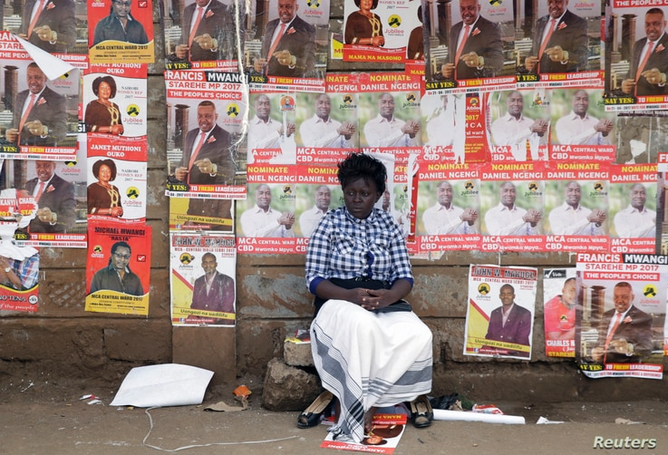 A woman sits in front of campaign posters as she waits to cast her ballot, during the Jubilee Party primary elections, at a polling centre in Nairobi, Kenya.