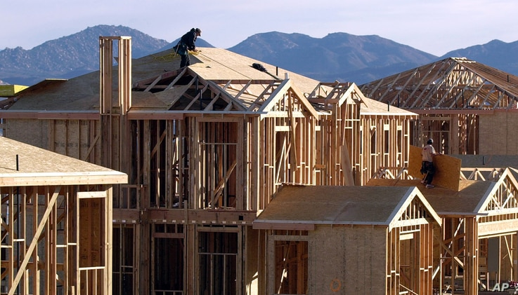 FILE - A worker prepares the roof of a new home for solar paneling in San Diego.