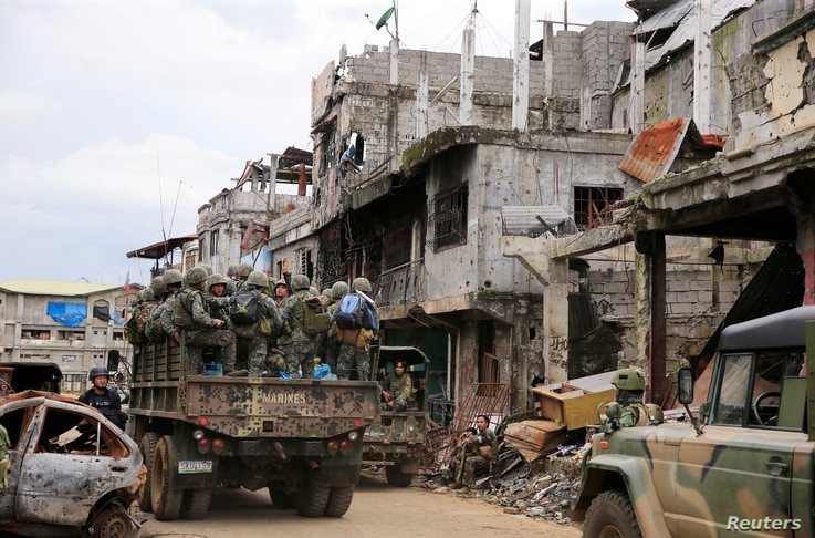 A military truck full of government soldiers move past damaged houses and buildings as troops continue their assault on clearing operations against the pro-IS militant group which seized Mapandi district in Marawi city, southern Philippines, Septembe...