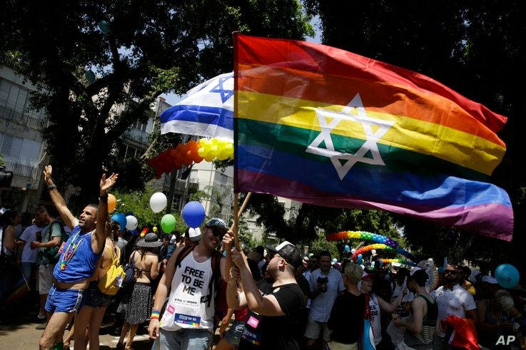 Israelis and tourists wave flags as they participate in the Gay Pride parade in Tel Aviv, Israel, June 8, 2018.