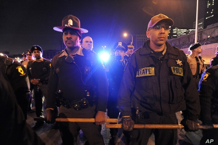 Authorities form a line to prevent protesters from entering an expressway in Chicago, Nov. 24, 2015. Officer Jason Van Dyke, who is white, shot Laquan McDonald, who is black, 16 times last year and was charged with first-degree murder Tuesday.