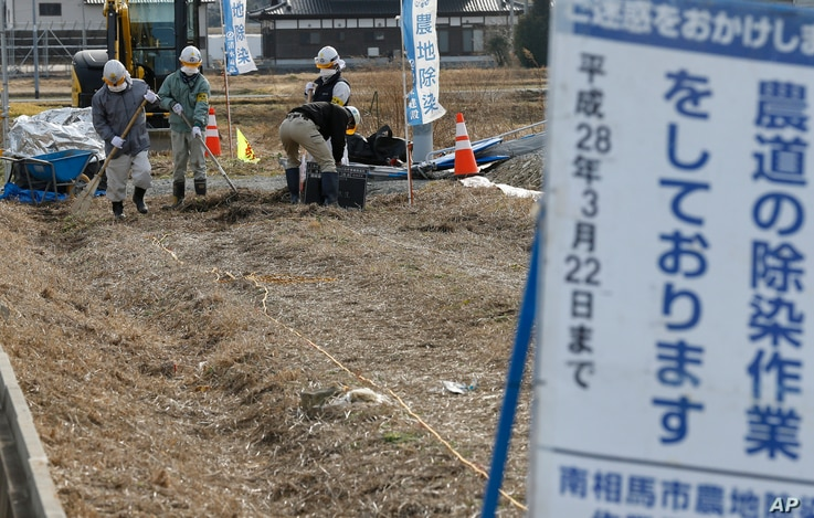 FILE - Workers clean a farm road during their decontamination work in Minamisoma, Fukushima prefecture, northeastern Japan, Feb. 24, 2016.
