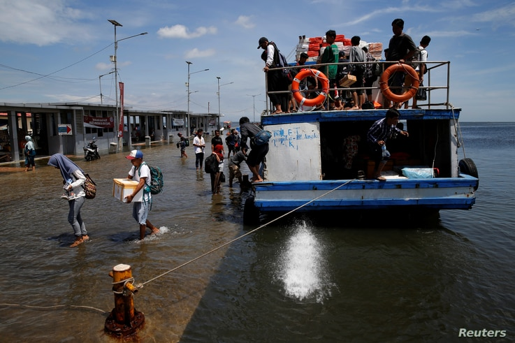 FILE - Passengers of a boat walk through rising sea water during high tide at Kali Adem port in Jakarta, Indonesia, Jan. 4, 2018.