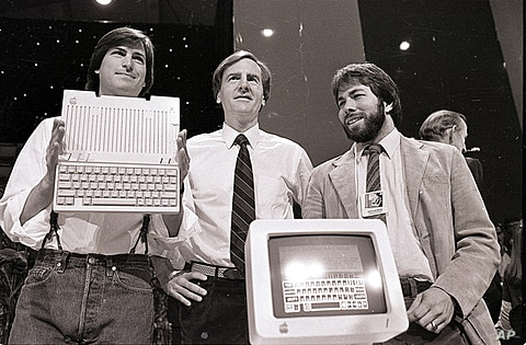 Steve Jobs, left, John Sculley, center, president and CEO of Apple, and Steve Wozniak, co-founder of Apple, unveil the new Apple II computer in San Francisco on April 4, 1984. (AP)