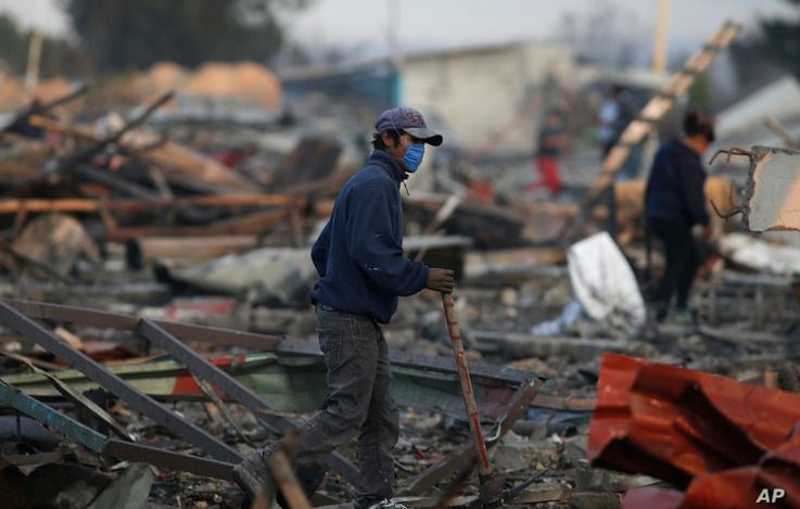A man walks  through the scorched ground of the open-air San Pablito fireworks market, in Tultepec, outskirts of Mexico City, Mexico, Dec. 20, 2016.
