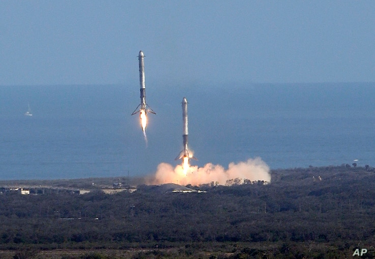 Two booster rockets from the Falcon 9 SpaceX heavy, return for a landing at the Kennedy Space Center in Cape Canaveral, Fla., Feb. 6, 2018.