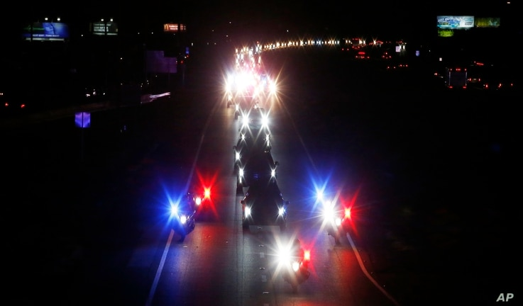 With a police escort, a long procession accompanies the hearse carrying the late Arizona Sen. John McCain along Interstate 17 on the way to Phoenix, Aug. 25, 2018, in Anthem, Ariz.