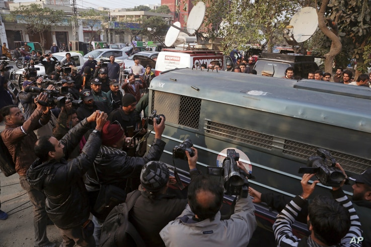 Surrounded by journalists and security forces, a prison van carrying Mohammad Imran, who is accused of the brutal killings of eight children in the eastern city of Kasur, arrives to a courthouse, in Lahore, Pakistan, Jan. 24, 2018.