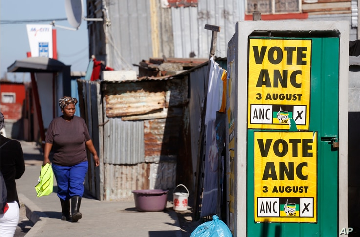 A woman, left, walks near an African National Congress, ANC, political poster fixed on a toilet door, that call South Africans to vote during municipal elections in the township of Khayelitsha on the outskirts of Cape Town, South Africa, Tuesday, Aug...